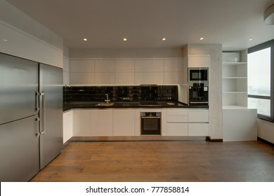 White kitchen with a black apron and a wooden floor
