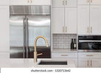White kitchen built with shaker style cabinets and white granite. Shows stainless steel oven, subway tile back splash and  refrigerator. Brushed gold faucet and hardware