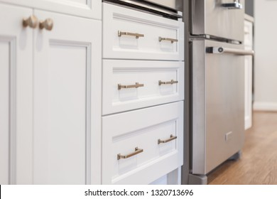 White kitchen built with shaker style cabinets. Shows cabinet details and brushed gold hardware knobs and pulls