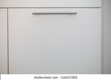 White kitchen cabinets with metal pulls or knobs on the doors