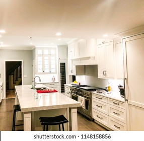 white kitchen design with glass cabinet, kitchen island with granite or marble or quartz counter top, undermount sink and faucet