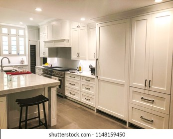 white kitchen design with glass cabinet, kitchen island with granite or marble or quartz counter top, gas stainless still stove undermount sink and faucet, ceiling and under cabinet lights