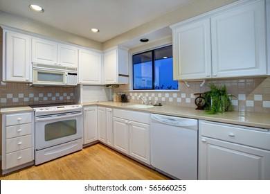 White kitchen design with white shaker cabinets paired with cream quartz countertops and white and beige subway tile kitchen backsplash, Northwest, USA