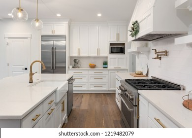 White Kitchen Detail in New Luxury Home: Includes Oven, Range,Stainless Steel Refrigerator, Hood, Cabinets, and Countertop