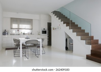 white kitchen and dining room with white epoxy floor and wooden stairs