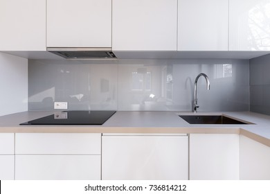 White kitchen with gray backsplash, sink and induction hob