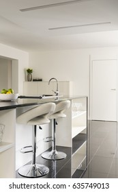 White kitchen interior with bar stools and kitchen island