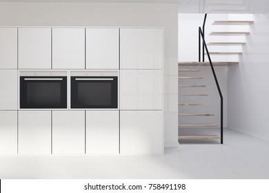 White kitchen interior with a concrete floor, white cupboard, built in oven and a stair leading to the second floor. 3d rendering mock up