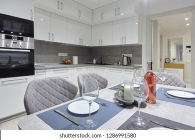 White kitchen interior with grey chairs and served table with white plates glasses and moss on the wall in new luxury home with lights on