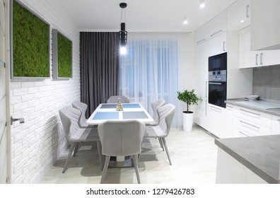 White kitchen interior with grey chairs,moss on the wall in new luxury home with lights on.