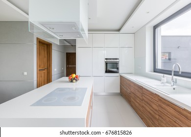 White kitchen with island, long countertop and wooden cupboards