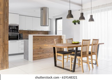 White kitchen with island, table and chairs