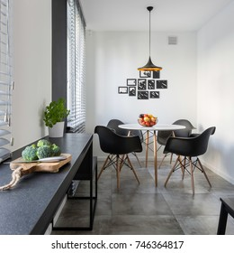 White kitchen with long, granite countertop, round table and chairs