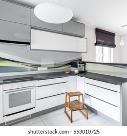White kitchen with modern pendant lamp and wooden step stool