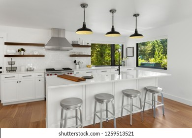 White Kitchen in New Luxury Home with Kitchen Island and Stainless Steel Appliances