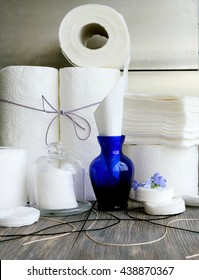 White kitchen paper towel, toilet paper, paper and cotton disks on a dark wooden table