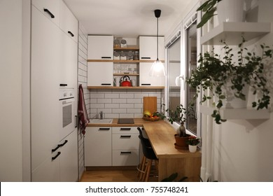 White kitchen with red components, cosy tine house
