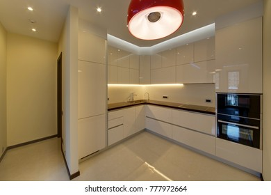 White kitchen with the red lamp and a white floor