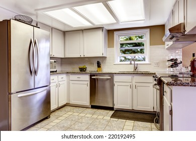White kitchen room with slklight and small window. White cabinets blend with steel appliances