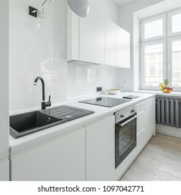 White kitchen with sink, worktop, simple cupboards and window