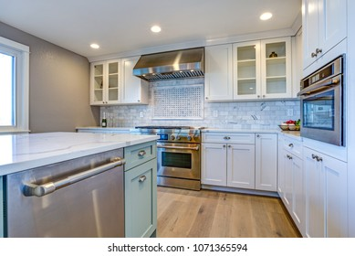 White Kitchen with stainless steel hood over gas cooktop and carrera marble backsplash.