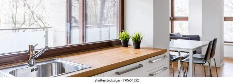 White kitchen with wooden countertop, silver sink and big window with blinds, panorama