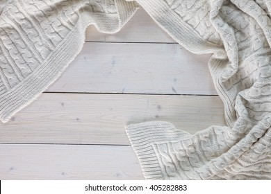 white knitted blanket. lying on white wooden floor in soft folds. in the centre of the empty place of inscription, text.