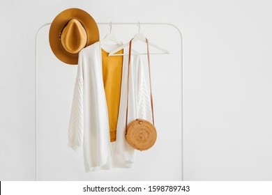 White knitted jumper on hanger with brown hat and bamboo bag on white background. Elegant  fashion outfit. Spring wardrobe. Minimal concept.