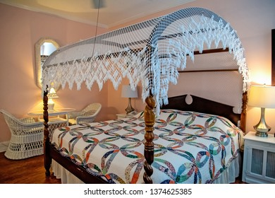 white lace canopy on four poster bed with old-fashioned quilt