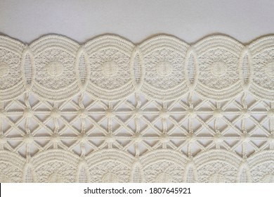 White lace. Close-up. Texture of white lace from cotton threads. Openwork. Linked pattern. Thread pattern. Geometric lace pattern. Seamless texture. White background. Abstraction