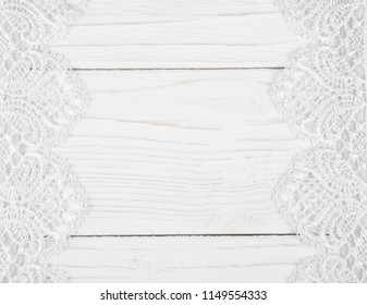 White lace on a worn white wooden background forming a frame with copyspace in the center (as a vintage background)