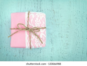 White lace and a simple bow on pink gift box on light blue wooden vintage background - concept for a girl's birthday or for mother's day