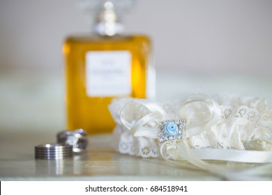 White lace wedding garter with fragrance bottle and wedding rings in background closeup bridal details