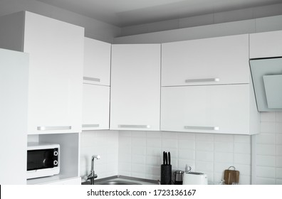 White lacquered kitchen facades on a comfortable kitchen. Modern white kitchen clean interior design.