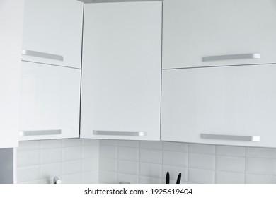 White lacquered kitchen facades on a comfortable kitchen. Modern white kitchen clean interior design.