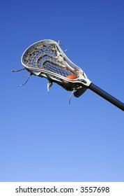 a white lacrosse stick against a blue sky