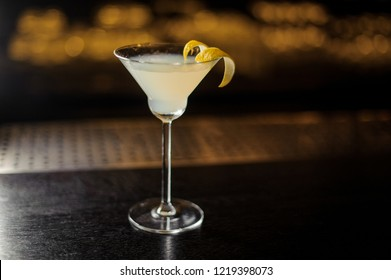 White Lady cocktail decorated with orange zest standing on the steel and wood bar counter on the blurred background