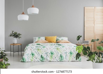 White lamps above bed with floral bedding and yellow pillow, real photo with copy space on the empty grey wall