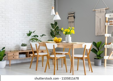 White lamps above wooden table and chairs in dining room interior with yellow flowers. Real photo