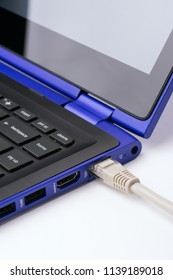 White LAN Internet cable plugged in  the port of a modern blue laptop