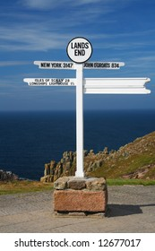 white Land's end directional sign over sea and cliffs background