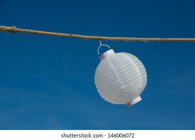 white lantern hanging on a weathered rope against a blue sky