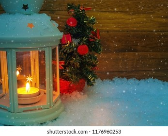 White lantern with lighting candle in the snowfall. In the background christmas tree with red decoration and wood planks.