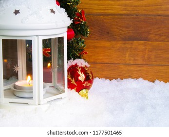 White lantern in the snow with lighting candle. In the background christmas tree with red decoration, ornament ball and wood planks.