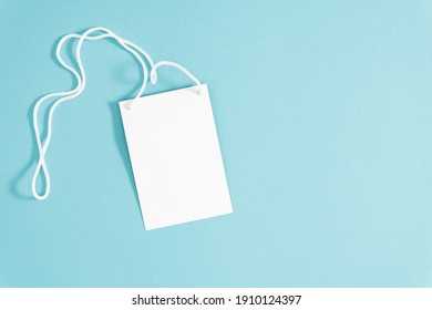 White lanyard and paper empty badge with blank space mock up  on blue background. Flat lay, top view, copy space