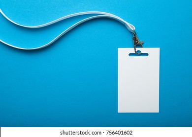 White lanyard and plastic badge with blank space mock up isolated on blue background.
