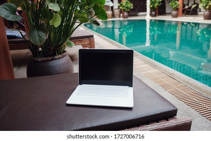 White laptop on the background of the pool in an exotic hotel.