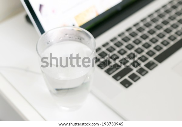 White laptop on table with glass of water