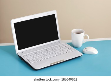 White laptop on table - place for text.