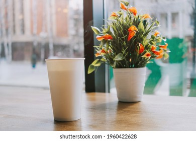 White large paper cup of tea on a table in a cafe. Behind a large window and a plant. The concept of a break, rest in a cafe. Copyspace.